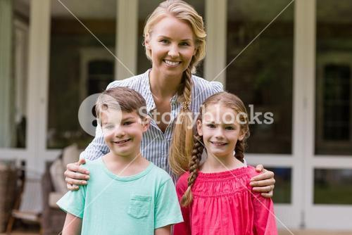 Smiling mother and kids standing outside home