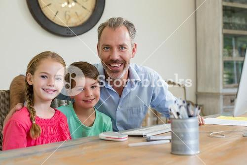Happy father and kids sitting at desk