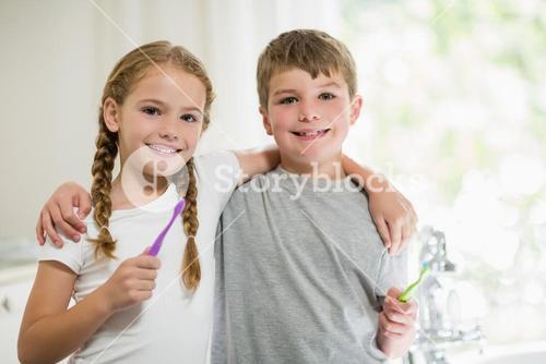 Siblings brushing teeth in bathroom