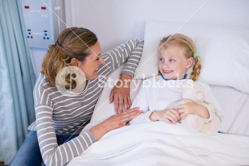 Mother talking to daughter in hospital bed