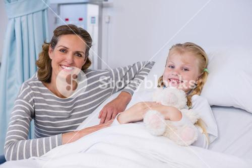 Portrait of mother and daughter in hospital bed
