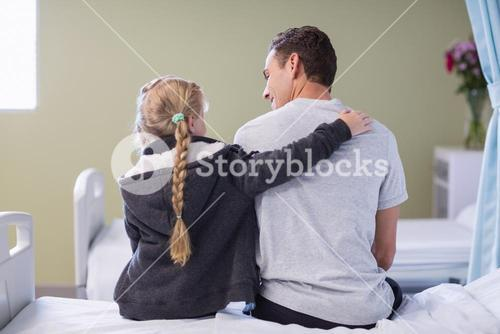 Rear view of daughter comforting her sick father