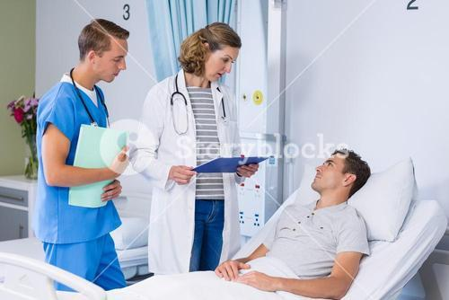 Doctors talking to patient in hospital bed