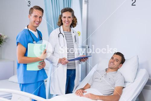 Portrait of doctors and patient in hospital bed