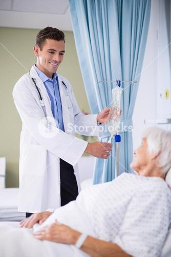 Doctor adjusting iv drip while patient lying on bed