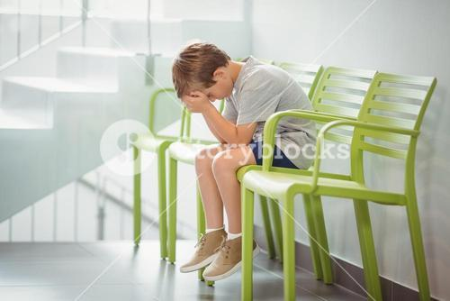 Upset boy sitting on chair in corridor