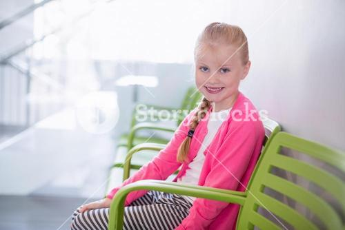 Portrait of smiling girl sitting on chair in corridor