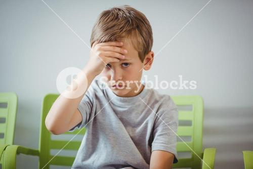 Portrait of upset boy sitting on chair in corridor