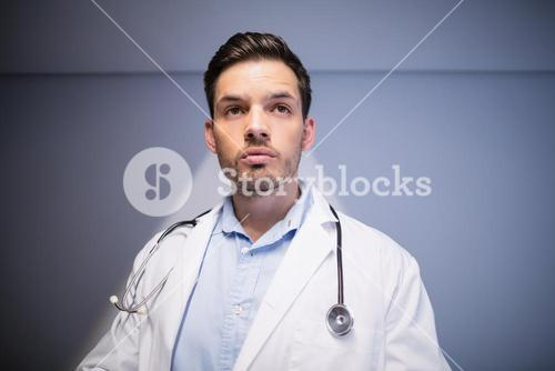 Thoughtful doctor standing in corridor
