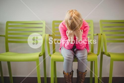Upset girl sitting on chair in corridor