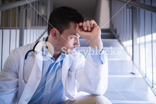 Thoughtful doctor sitting on staircase