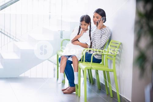Mother talking on mobile phone while girl sits on her lap