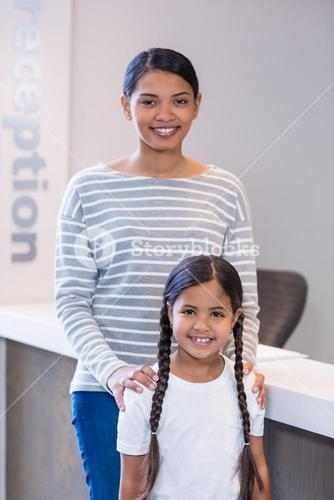 Portrait of smiling mother and daughter standing at counter