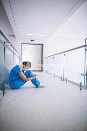Sad nurse sitting on floor in corridor