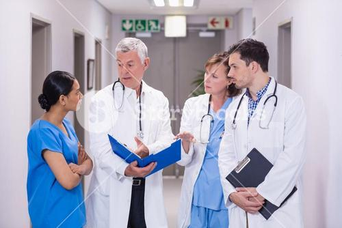 Nurse and doctors discussing over clipboard
