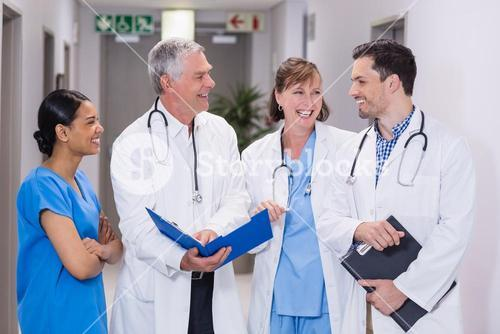 Smiling nurse and doctors discussing over clipboard