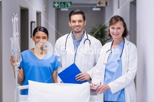 Portrait of doctors and nurse standing together by hospital bed