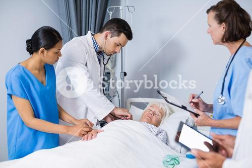 Doctors examining patient in ward