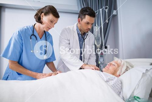 Doctors examining senior patient with stethoscope