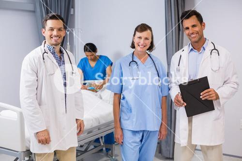 Portrait of doctors and nurse standing with medical report