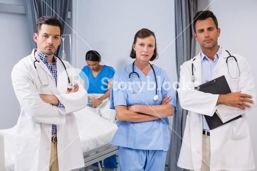 Portrait of doctors and nurse standing with arms crossed