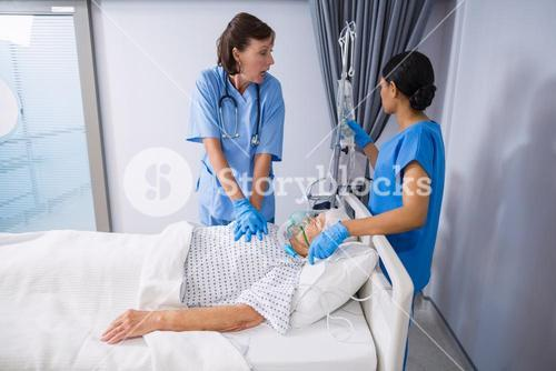 Doctor and nurse treating senior patient in ward