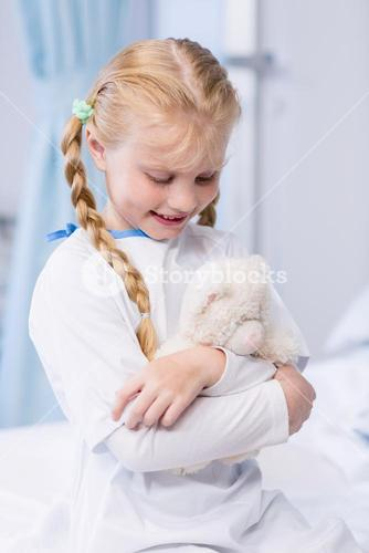 Sick girl with teddy bear in hospital bed