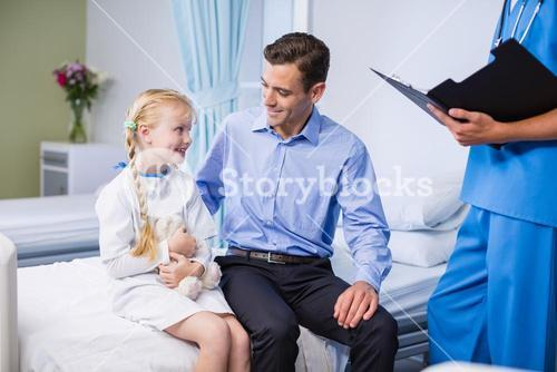 Sick girl and father in hospital bed