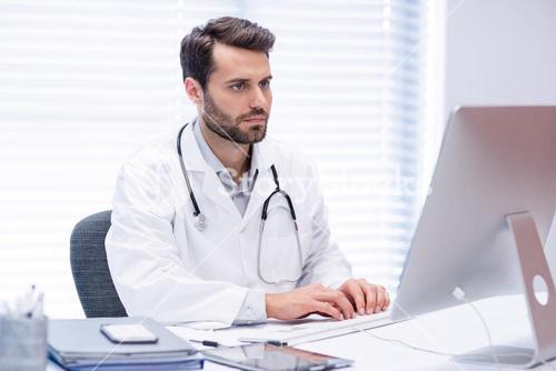 Male doctor working on personal computer