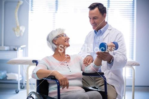 Physiotherapist assisting senior patient with hand exercise