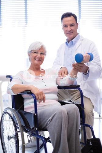 Portrait of physiotherapist assisting senior patient with hand exercise
