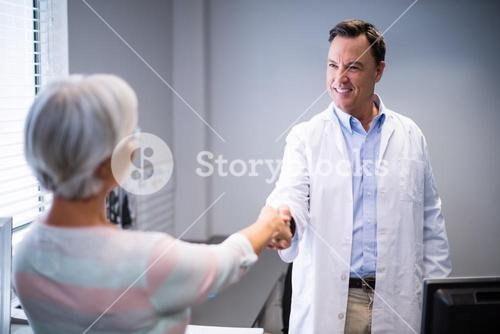 Doctor shaking hands with senior woman