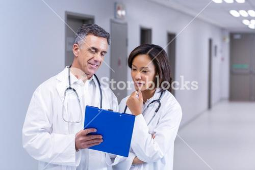 Doctors having discussion on clipboard in corridor