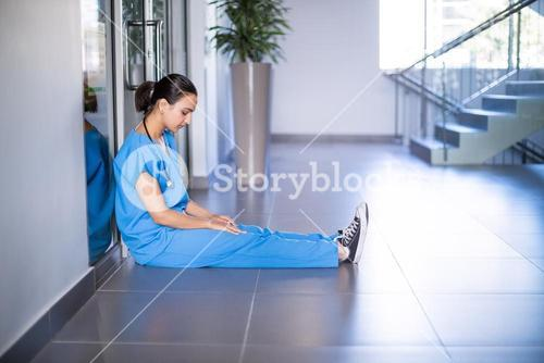 Tensed female doctor sitting in corridor