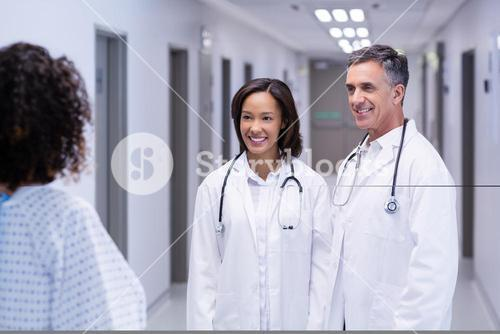Female patient interacting with doctors in corridor