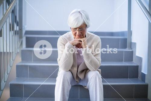 Upset senior woman sitting on stairs