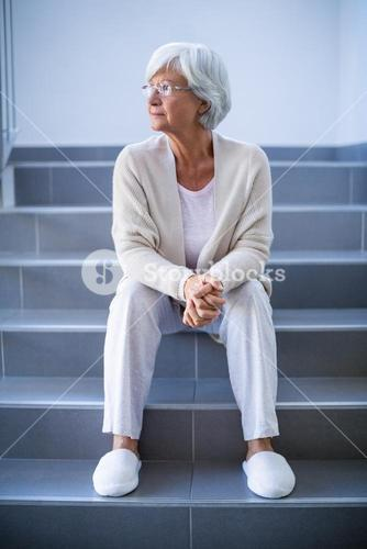 Thoughtful senior woman sitting on stairs