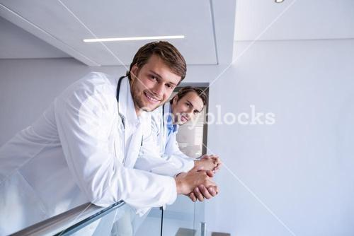 Portrait of smiling doctors leaning on railing in corridor