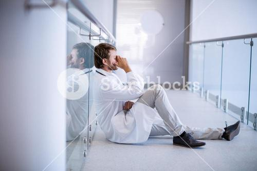 Tensed doctor sitting in corridor