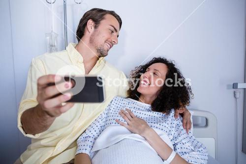 Couple interacting while taking selfie in ward