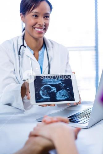 Doctor showing babies ultrasound scan on digital tablet