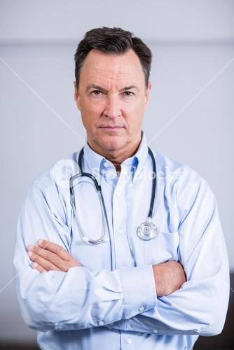 Portrait of confident doctor standing with arms crossed