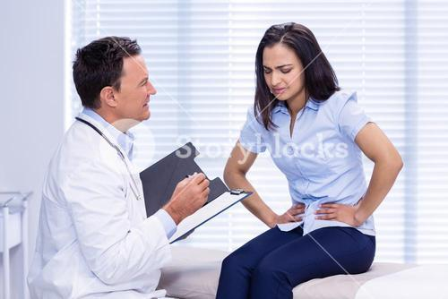 Patient suffering from stomach ache while consulting doctor