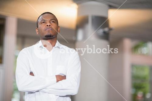 Thoughtful businessman standing in conference centre