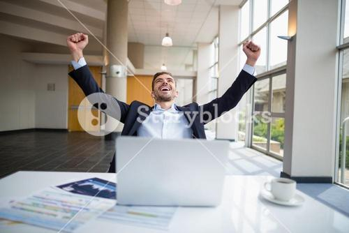 Businessman sitting at desk with arms outstretched