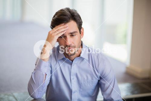 Worried businessman with hand on head