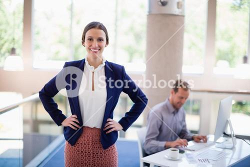 Happy and confident businesswoman standing with hands on hip