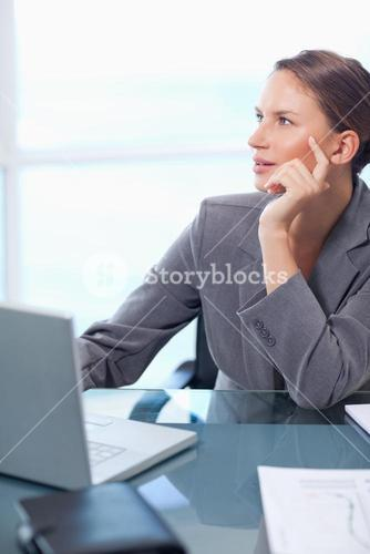 Portrait of a doubtful businesswoman working with a laptop