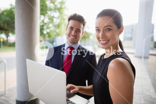 Businessman and colleague holding laptop
