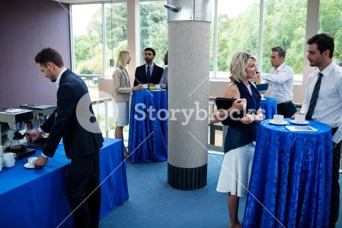 Business executive taking coffee from coffee maker